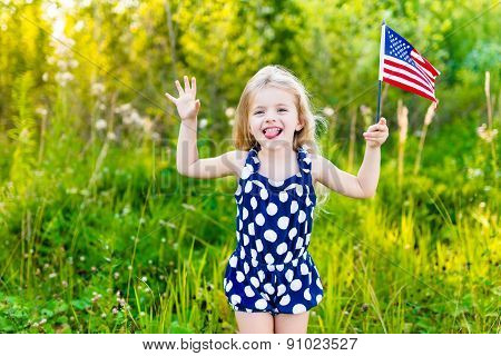 Funny Little Girl With Long Curly Blond Hair Putting Out Her Tongue And Waving American Flag