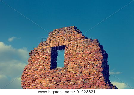 Fragment Of Ancient Ruined Building With Window On Blue Sky Background.