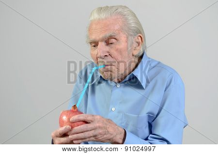 Senior Man Drinking Fresh Pomegranate Juice