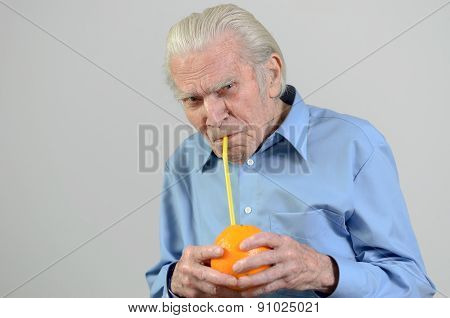 Senior Man Drinking Fresh Orange Juice