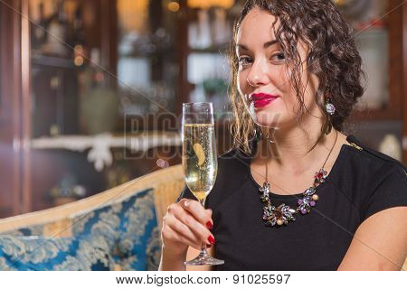 Beautiful young brunette woman drinking champagne.