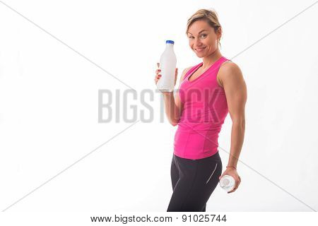 Girl athlete in sportswear, posing on a white background, holding a bottle of water or milk.