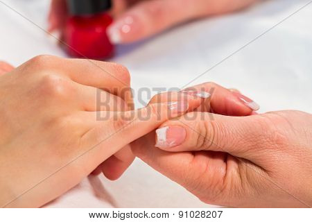 Manicure in the spa salon. Drawing of red nail polish.