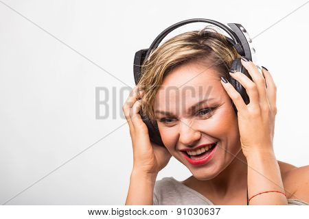 Blonde girl with headphones. Girl in headphones listens to music.