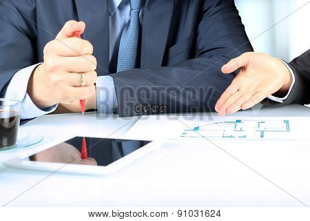 Real-estate Agent Showing House Plans To A Businesssman