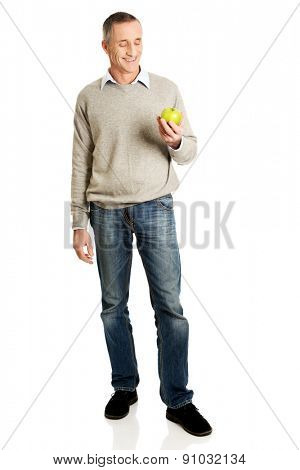 Full length mature man with an apple.