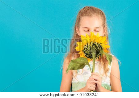 Girl With Closed Eyes Smelling A Sunflower