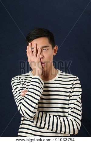Frustrated young Asian man covering his face by palm