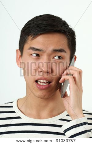 Angry young Asian man using a smartphone.
