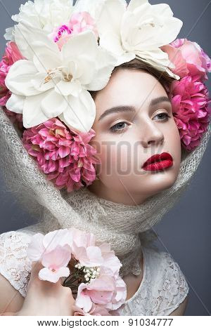 Beautiful girl in a headscarf in the Russian style, with flowers on the head and red lips.