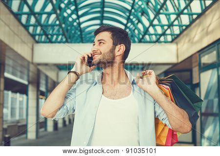 Young Man Using Phone And Holding Shopping Bags
