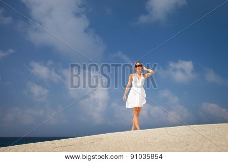 Pretty young woman outdoors, enjoying the sunlight and sea breeze while on vacation