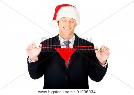 Portrait of santa businessman stretching female thongs.
