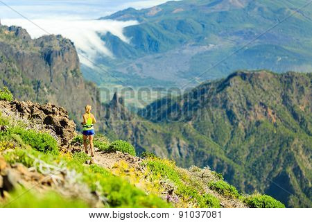 Woman Running In Mountains On Sunny Summer Day