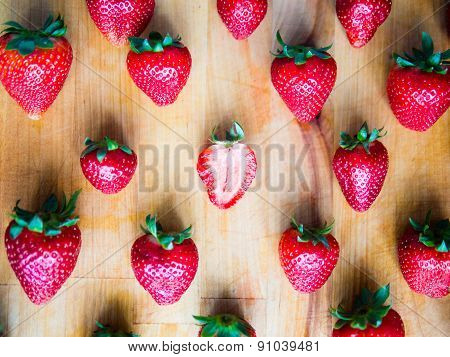 One Cutted Strawberry In An Srranged Pattern Of Strawberries On A Wooden Board, Difference