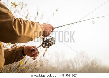 Fisherman on the autumn background. Fisherman in his hand holding spinning.