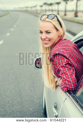 Happy Young Woman Looking Out From Car Window