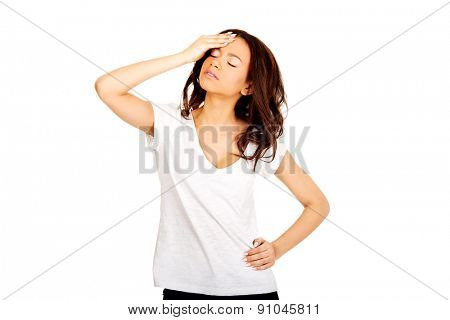 African teen with a headache holding head.