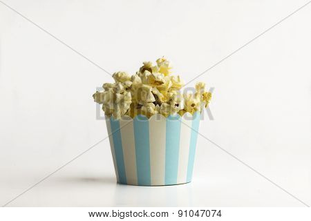 Popcorn in a tiny paper bucket on white background - a concept