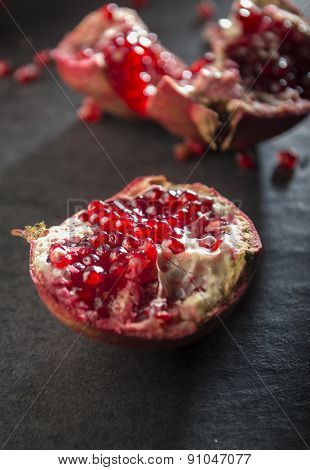 Smashed pomegranate on black background. Selective focus treatment.