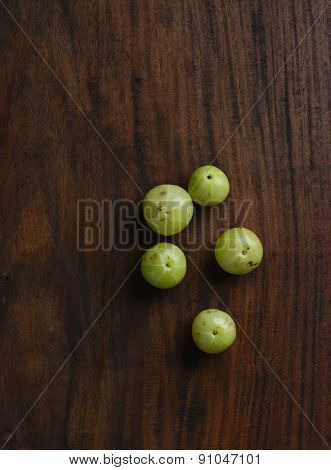 Few Indian gooseberries placed on wooden background. Top angle.