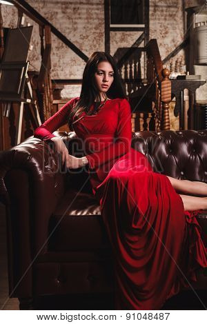elegant sensual young woman in red dress sitting on leather sofa