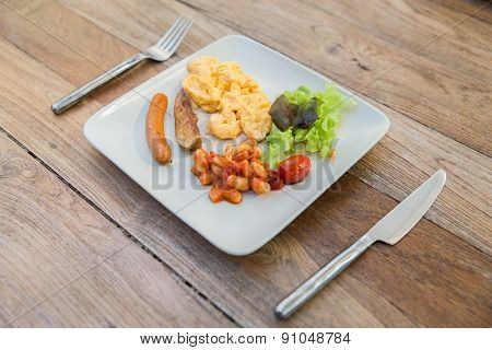 cooking, kitchen and food concept - plate with sausage, eggs, beans and garnish on wooden table at restaurant