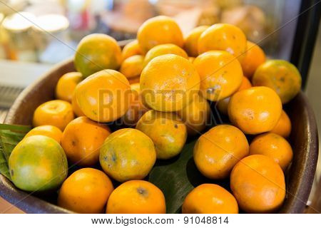 cooking, kitchen, vegetarian food, fruits and citrus concept - basket of of fresh ripe oranges fruits at kitchen