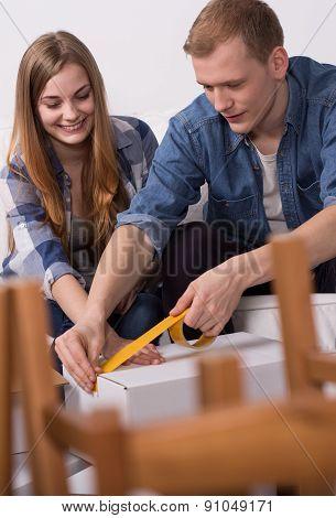 Couple Sealing A Moving Box