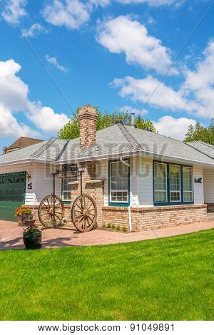Cozy house with wagon wheel decoration. Home exterior.