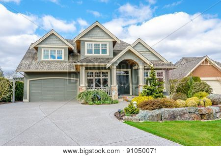 Luxury house with a two-car garage and beautiful landscaping on a sunny day. Home exterior.