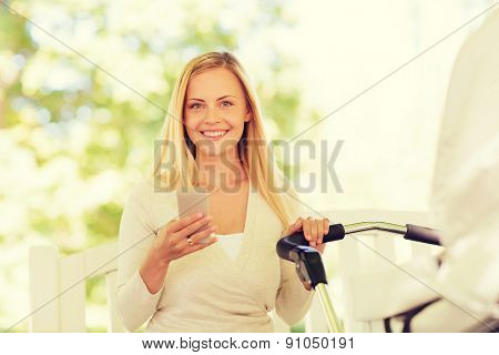 family, parenthood, technology and people concept - happy mother with with smartphone and baby stroller in park