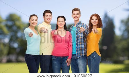 friendship, summer vacation, nature and people concept - group of smiling teenagers pointing finger on you over green park background