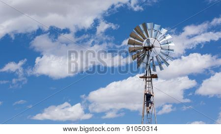 Man Climbing Windmill And Beautiful Blue Sky.