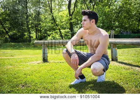 Shirtless athletic young man resting in city park, sitting