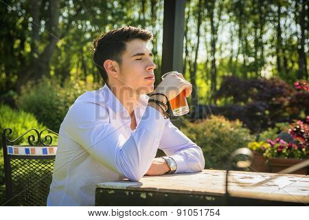 Handsome young man sitting alone at table outside in park