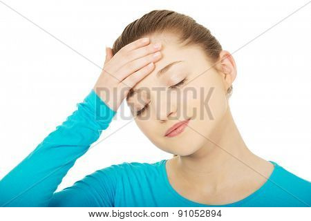 Teen woman with headache holding her head.
