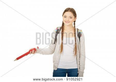 Happy schoolgirl pointing down with pencil.