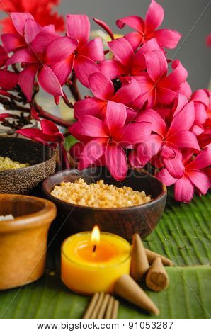 spa setting with branch red Frangipani on banana leaf
