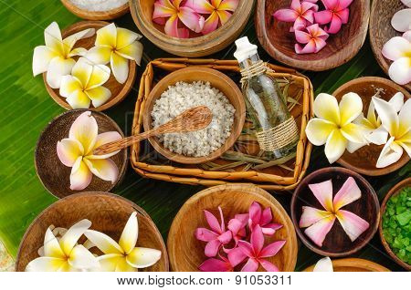 spa setting with massage oil , salt in bowl , frangipani,spoon