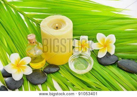 frangipani and candle ,oil ,black stones on palm leaf