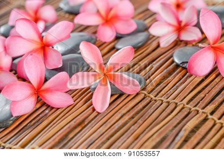 Set of frangipani with set of black stones on mat texture