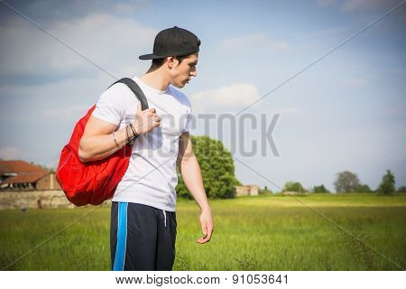 Handsome young man outdoor hiking on rural road