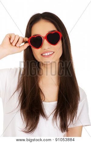 Teenage woman wearing heart sunglasses.