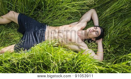 Fit muscular shirtless young man relaxing lying in a field