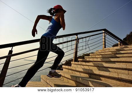 healthy lifestyle sports woman running on stone stairs sunrise seaside