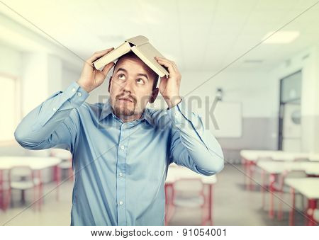portrait of teacher shield himself with book