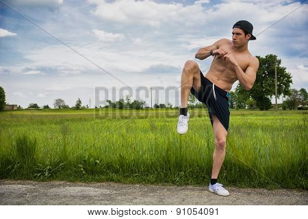 Shirtless athletic young man outdoor practicing martial arts