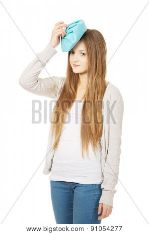Teen woman with headache and ice bag.