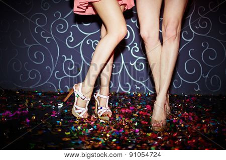 Legs of two girls dancing in night club